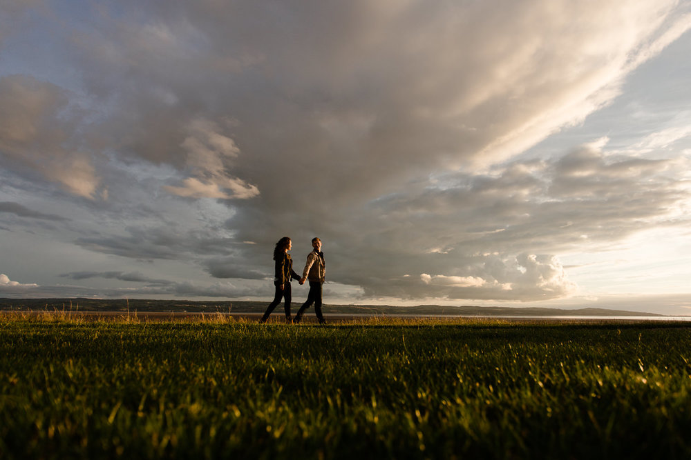 A couple walking past epic Wirral skies - Merseyside pre wedding shoot