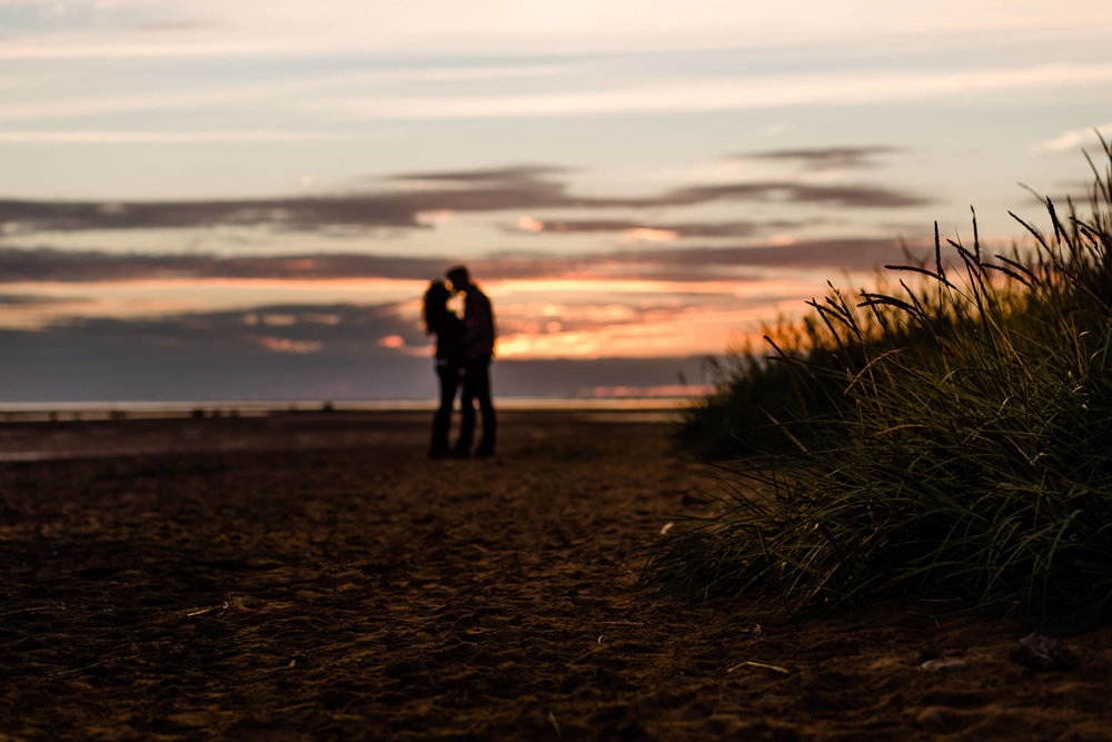 A couple silhouetted against the sunset key on the beach couple shoot