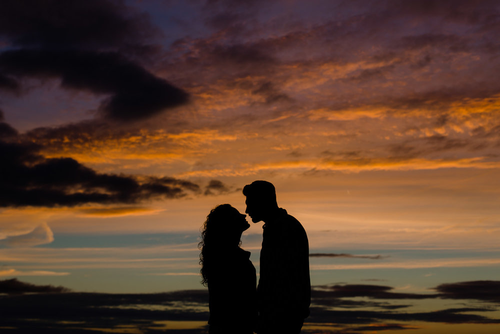 Colourful sunset sky with a silhouette of a couple on their pre wedding shoot - Merseyside Wedding Photographers