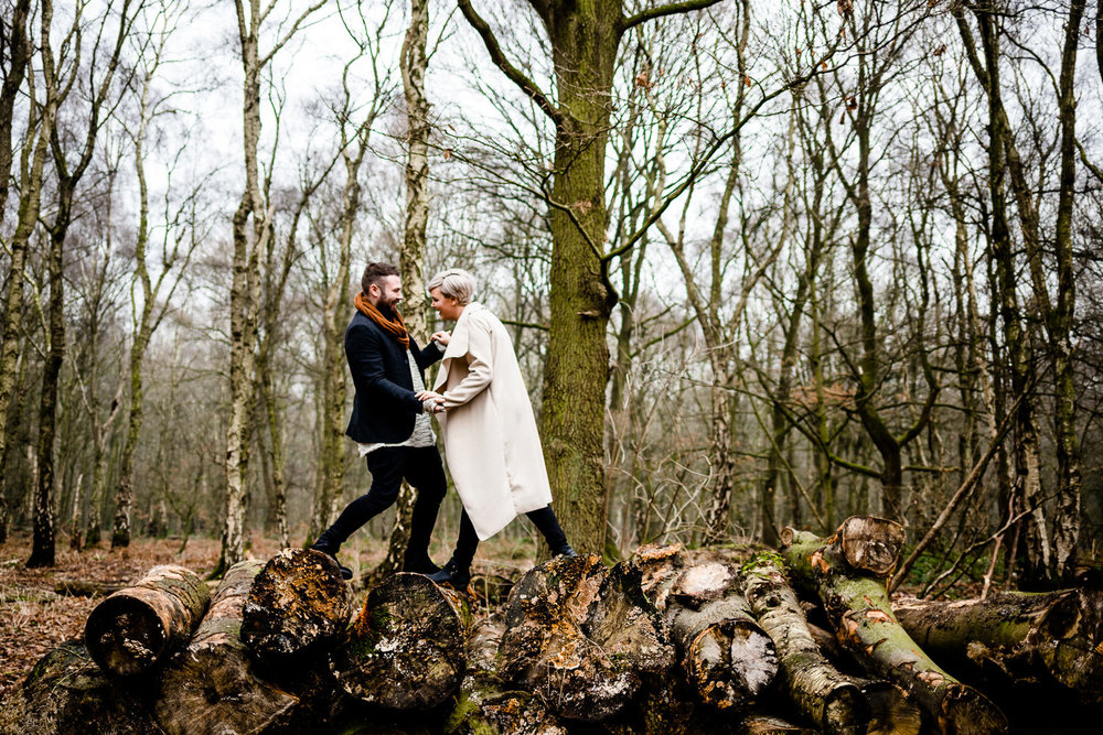 Couple climb on a pile of logs on a woodland engagment shoot, Yorkshire wedding photographer