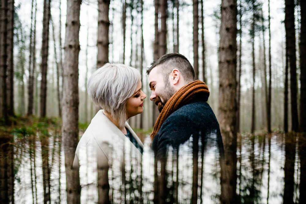 Engaged couple almost kissing surrounded by pine trees with reflection, wedding photographer in Yorkshire