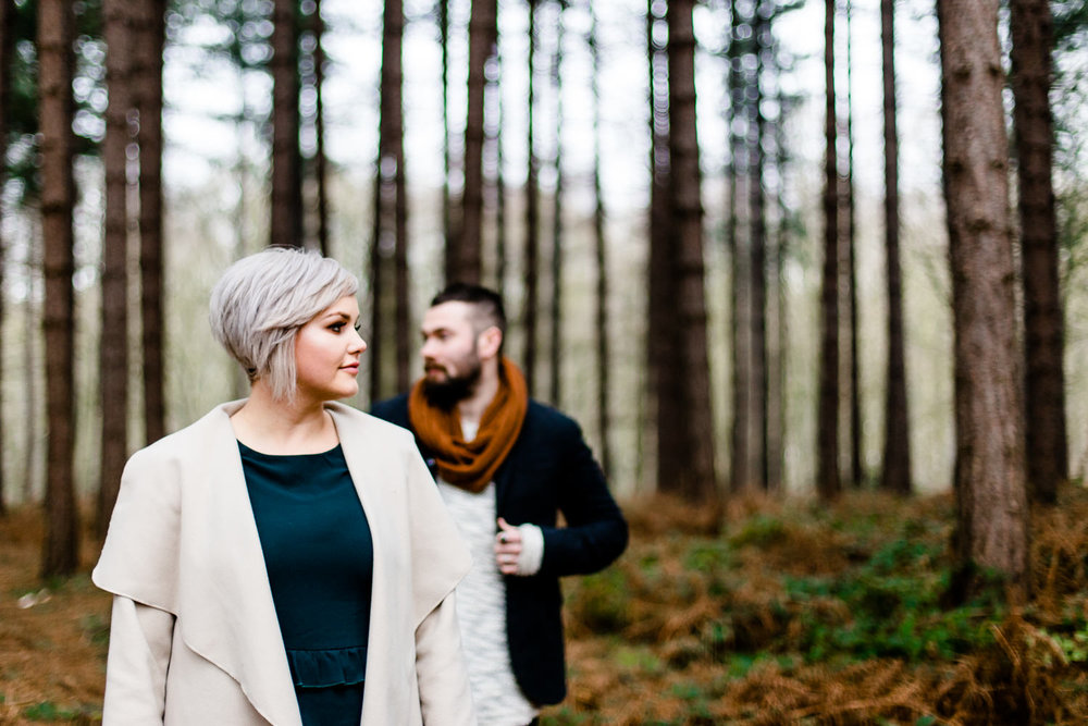 An engaged couple stood among pine trees on their pre wedding shoot in Yorkshire
