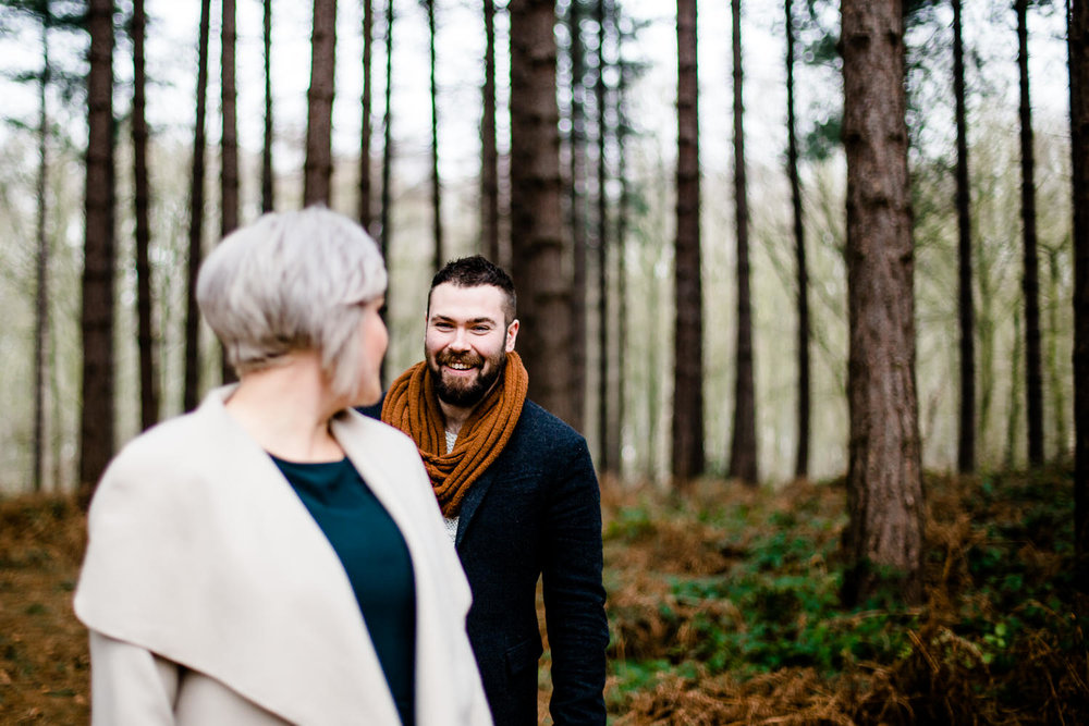 man and woman looking at each other stood among pine trees