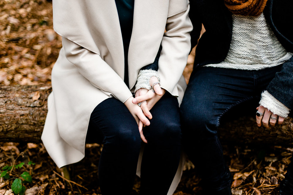 An engaged couple holding hands sat on a tree on a shoot