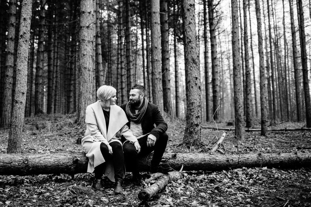 Fiances sat on a fallen pine tree in woodland on their engagement shoot