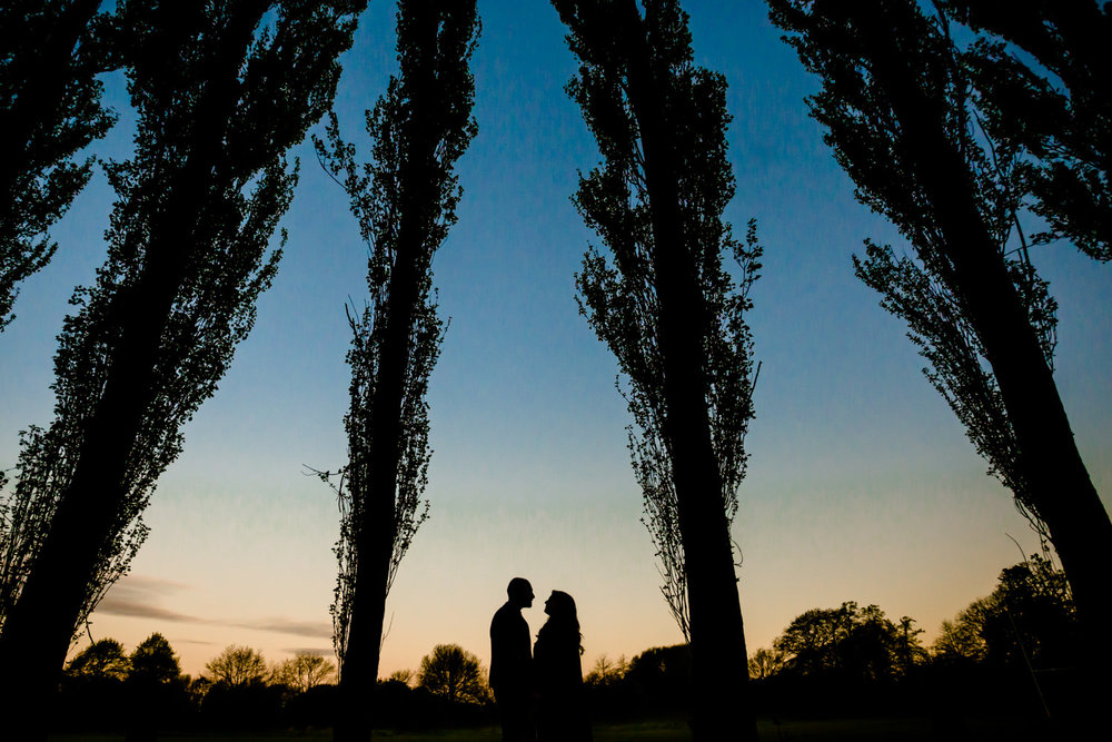 Silhouette of couple on an enagement shoot stood between trees against sunrise sky on thier pre wedding shoot in Fletcher Moss park, Didsbury, Manchester.