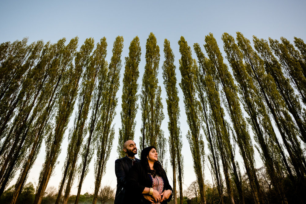 Hugging couple in front of a row of tall trees on their engagement shoot in a Manchester park.