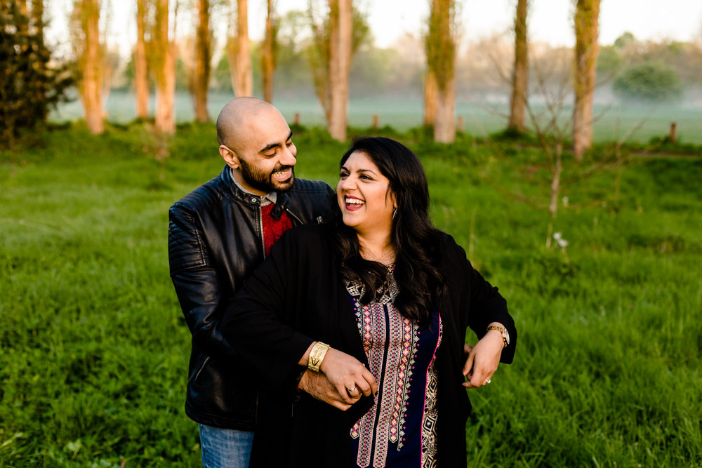 Couple laughing on their Hindu pre wedding shoot in a Manchester park