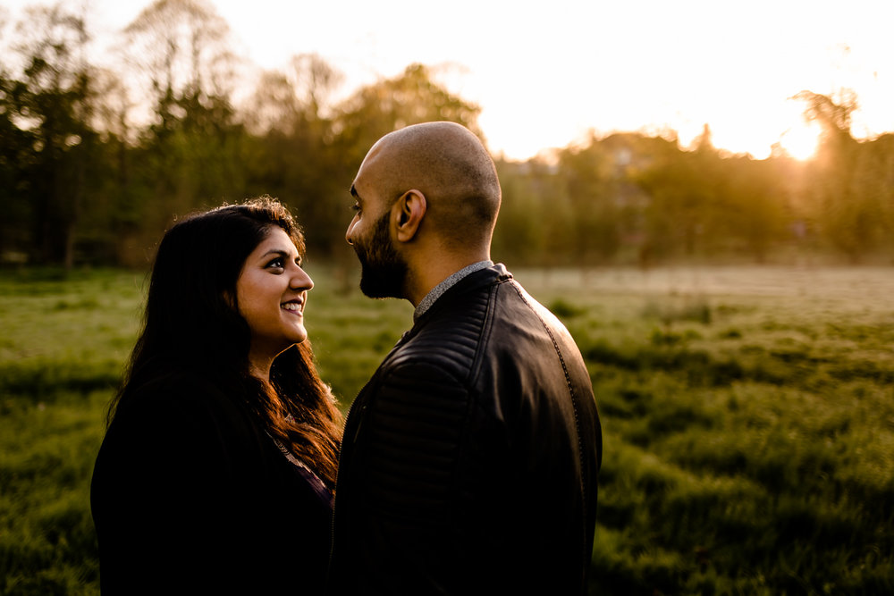Couple looking at each other in the golden light of a sunrise over parkland