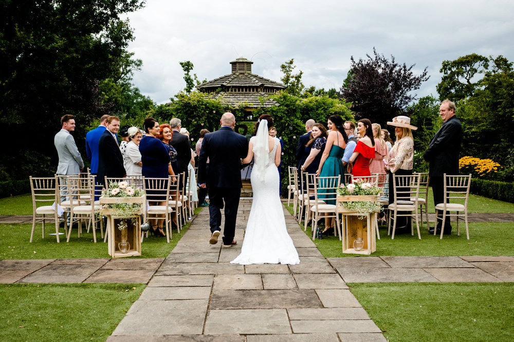 Wide shot of bride walking down the isle at an outdoor garden ceremony at Pryor Hayes, Cheshire