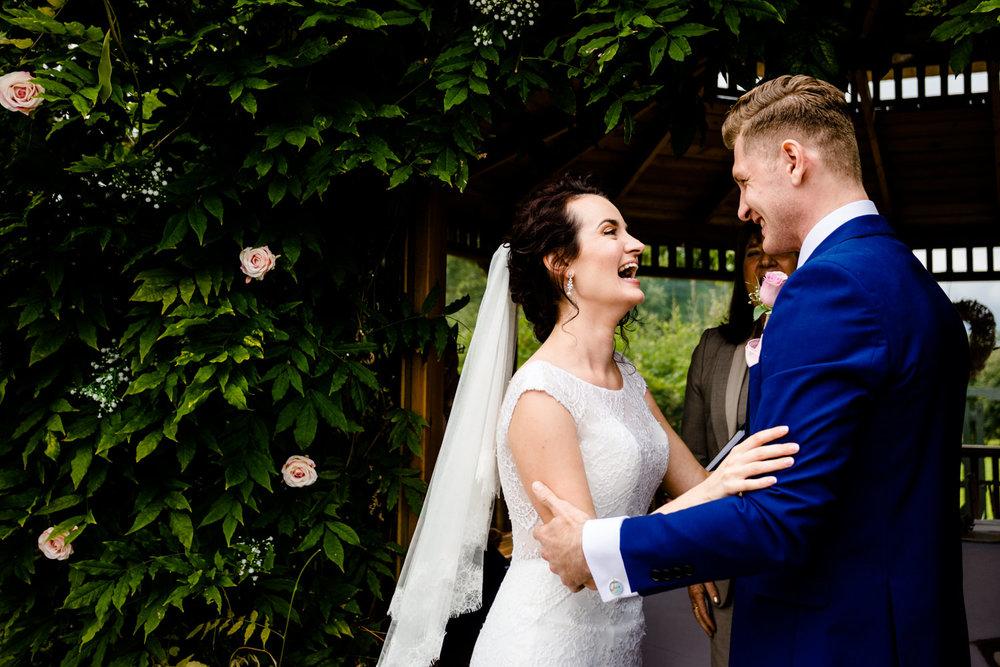 Outdoor garden ceremony , bride smiling at her groom, in Cheshire.