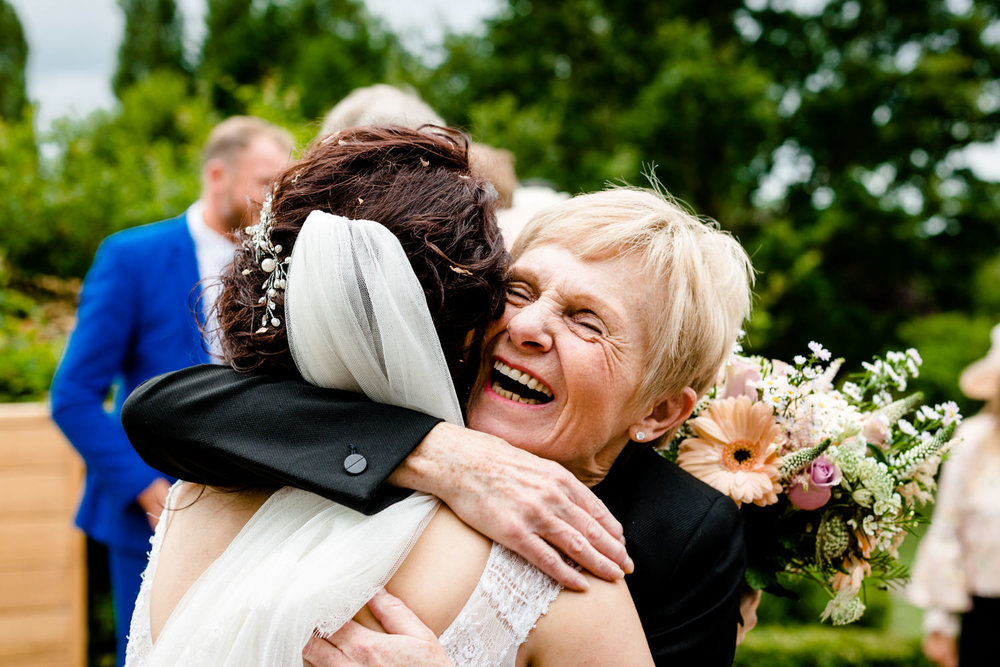 Guest smiling and hugging the bride at Pryors Hayes in Cheshire.