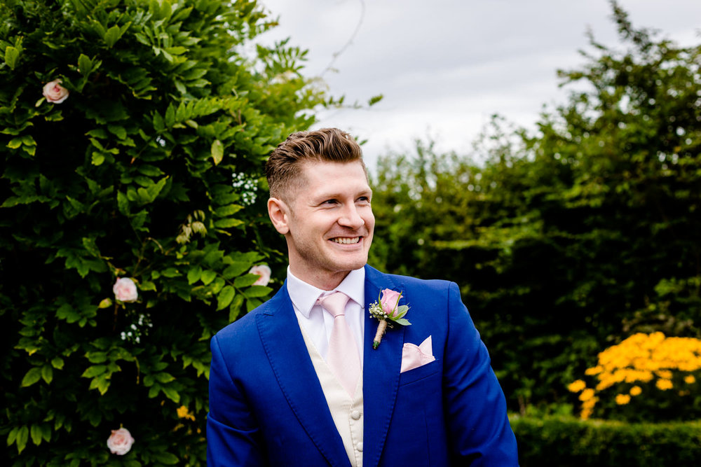 Groom at the front of his wedding ceremony smiling at his bride coming down the isle in Cheshire