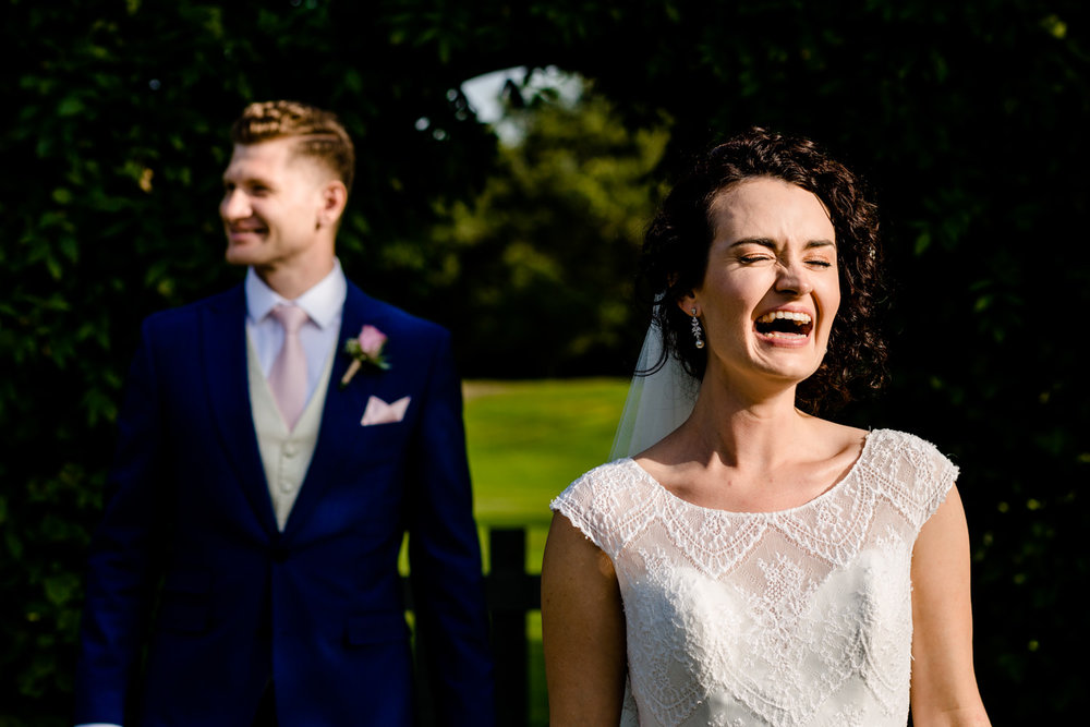 Bride laughing alongside her groom in the wedding garden at Pryor Hayes in Cheshire wedding photography