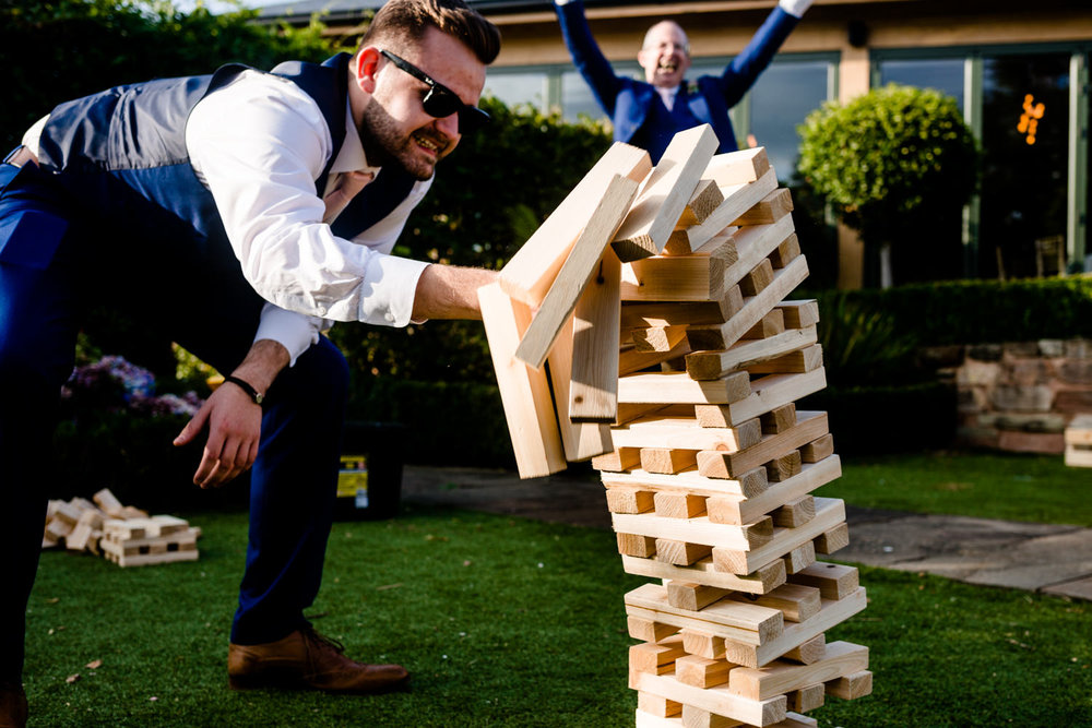 Giant Jenga lawn game falling over at a wedding.