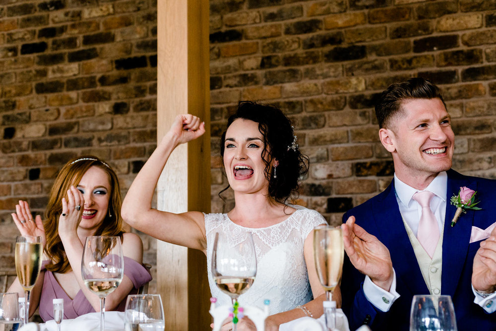 Laughing bride and groom during speeches in Pryor Hayes modern barn venue.