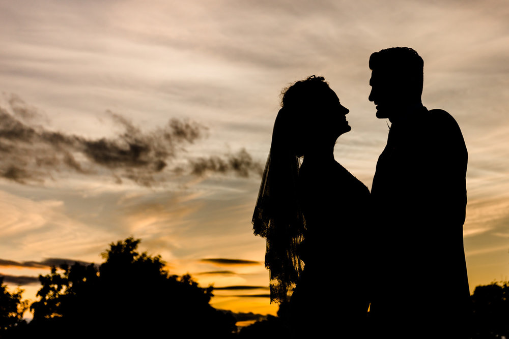 Sunset sky with silhouette of married couple.