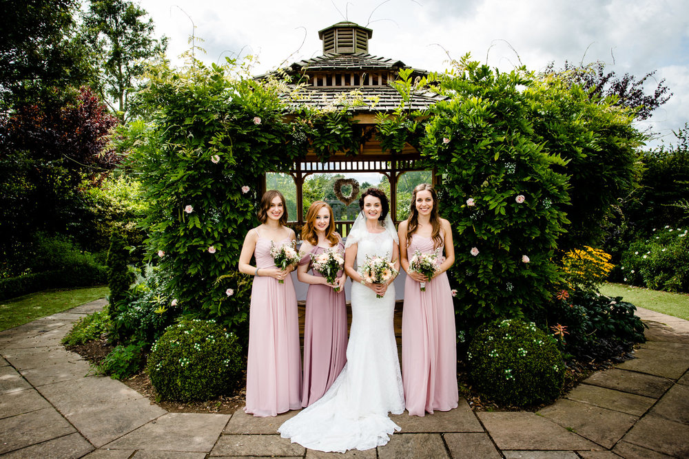 Bride and her bridesmaid stood in front of the garden pagoda at Pryors Hayes in Cheshire.