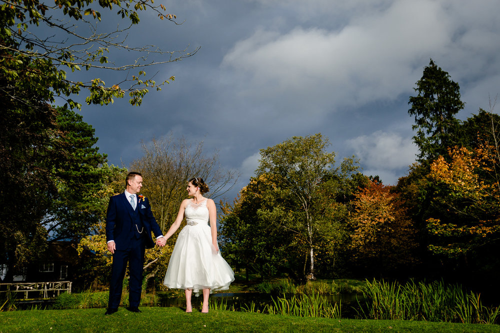 A bride and groom holding hands stood by a lake in front of autumn trees at Thornton Manor in Wirral