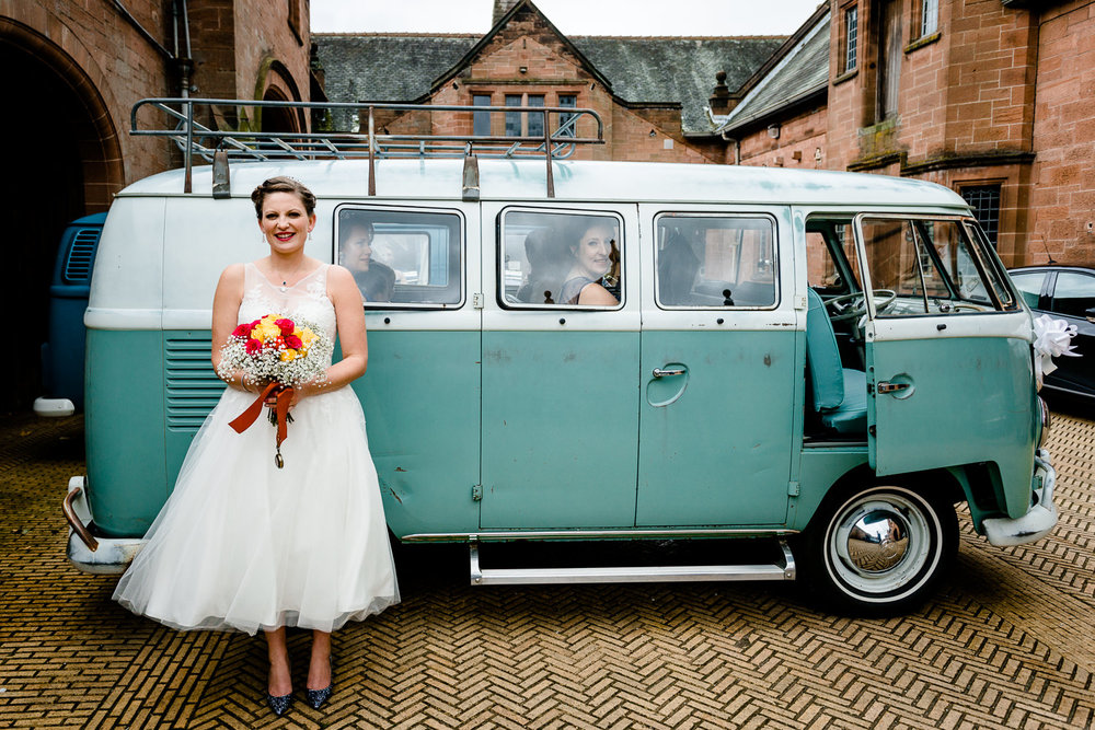 Kate, the bride, in a tea length wedding dress stood by a vintage green VW camper van in Cheshire wedding venue in Wirral, Thornton Manor.