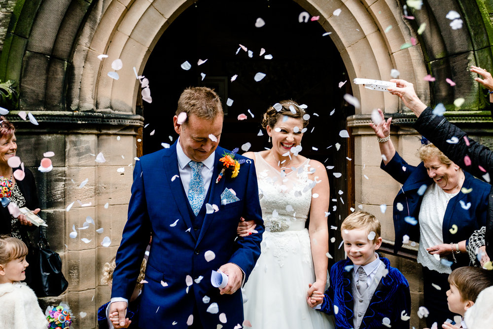 Confetti being thrown over a bride and groom outside a wedding at Christ Church in Bebington, Wirral.