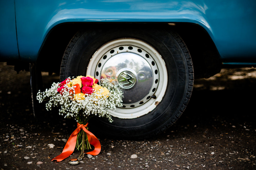 A colourful bouquet and blue VW camper van at a wedding in Cheshire at Thornton Manor.