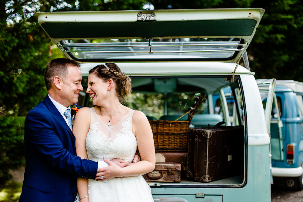 A bride and groom cuddle in front of a green vintage VW camper van by Thornton Manor wedding photographers.