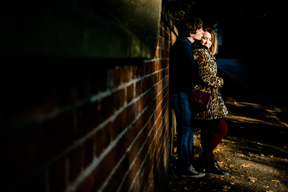 An engaged couple cuddle leant against a wall in a pool of sunlight, Didsbury Wedding Photographer