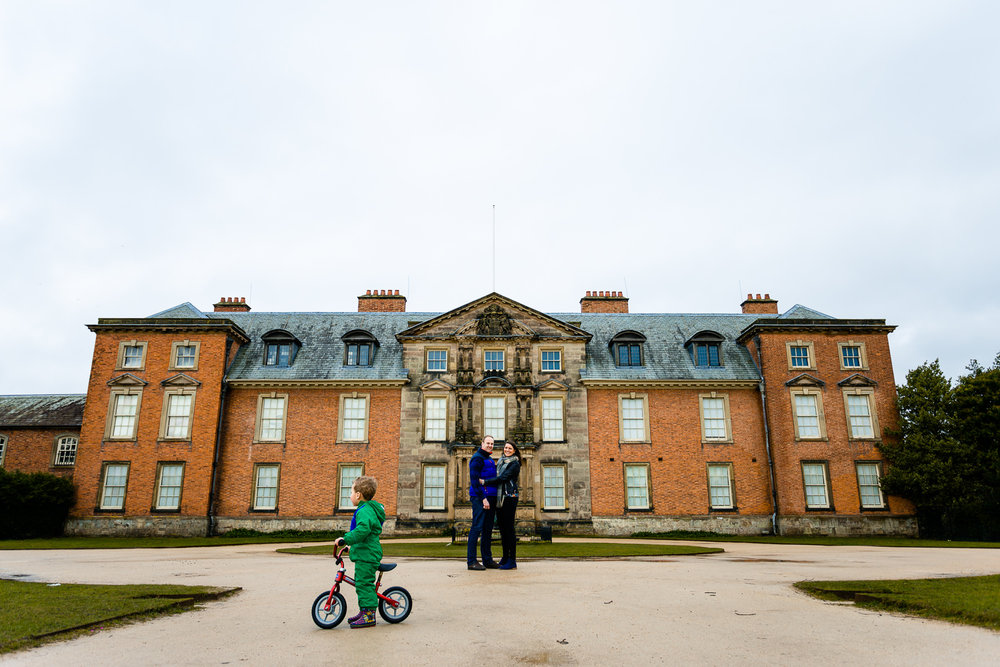 A couple on their pre wedding shoot stood in front of the house at Dunham Massey.