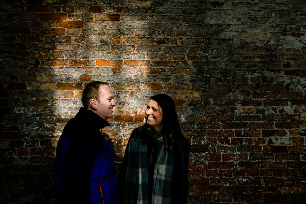 Relaxed, laughing couple lit my sunlight through a window on their pre wedding shoot.