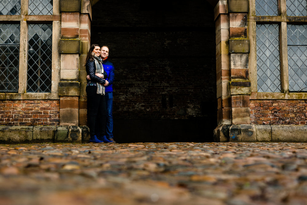 A Dunham Massey pre wedding shoot image of a couple stood in an archway.