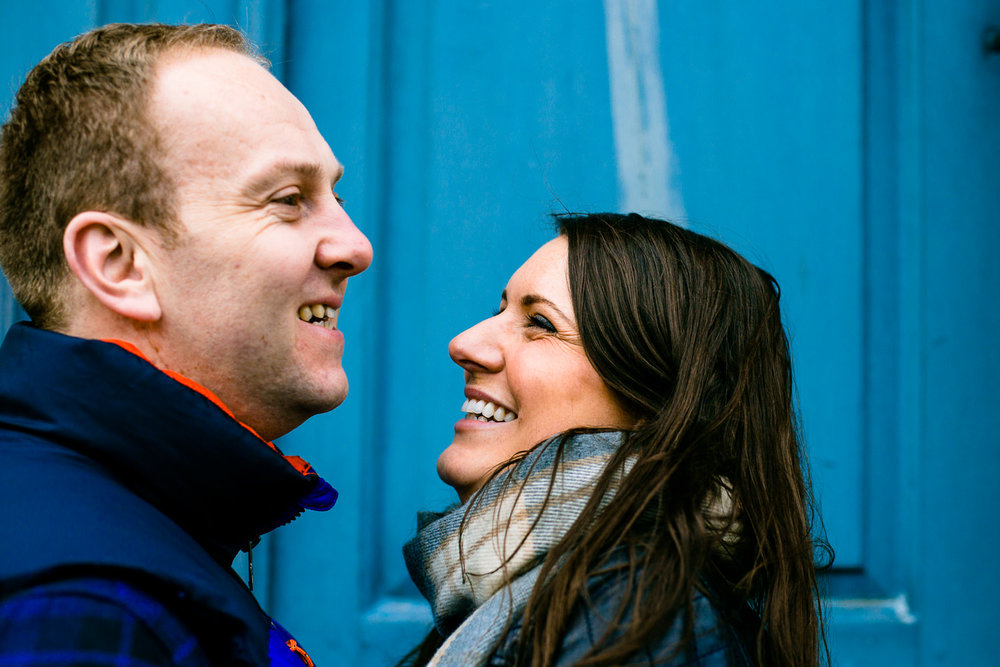 Claire and Damien laugh in front of a blue door at Dunham Massey.