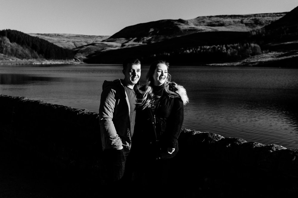 A couple laughing on their pre wedding shoot next to a reservoir.
