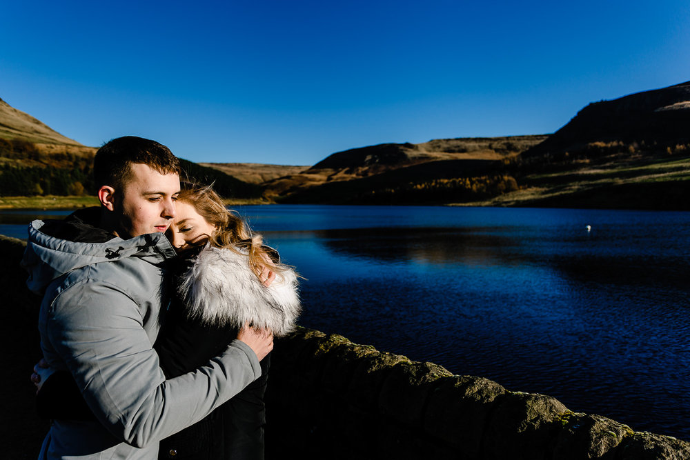 An engaged couple keep each other warm beside the deep blue Dovestone reservoir, pre wedding shoot by Manchester wedding photographers.