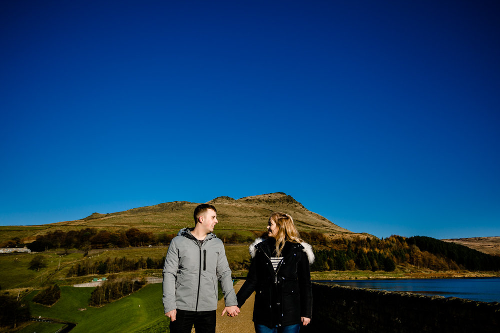 Sarah and Jason stand in front of a beautiful landscape on a sunny Manchester winters day on their Dovestone Reservoir pre wedding shoot.