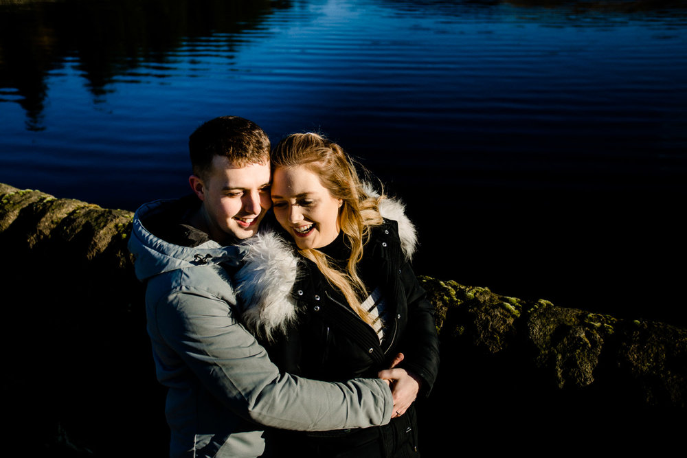 Cute couple, Sarah and Jason laughing and cuddling on their pre wedding shoot at Dovestone reservoir.