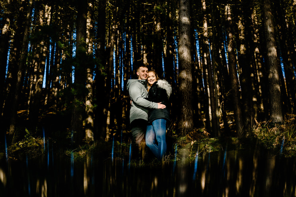 Manchester wedding photographers capture a couple in beautiful dappled light among pine trees at Dovestone reservoir on their pre wedding shoot.