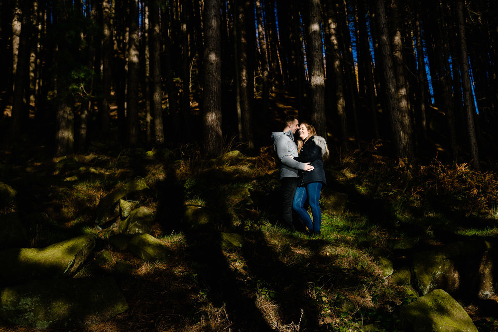 A couple stood in dappled light under pine trees.