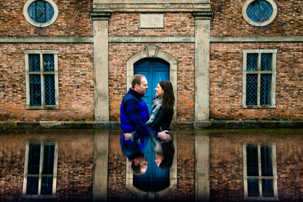 Dunham Massey pre wedding shoot, reflection image of a couple stood in front of an old building.