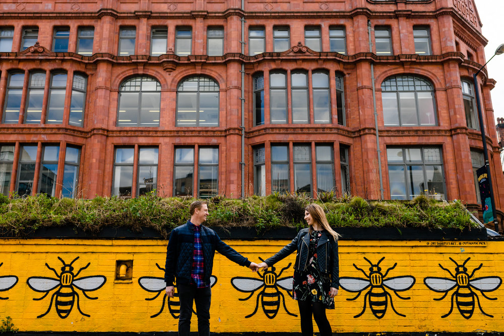 Urban pre wedding shoot in Manchester's Norther Quarter, a couple hold hands stood in front of a wall mural of the iconic yellow Manchester bees.