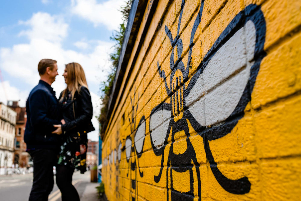 A couple stood next to the Manchester Bee wall art in the Northern Quarter on their pre wedding shoot.