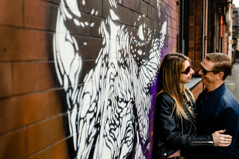 A cople cuddle in front of Norther Quarter street art on their pre wedding shoot.