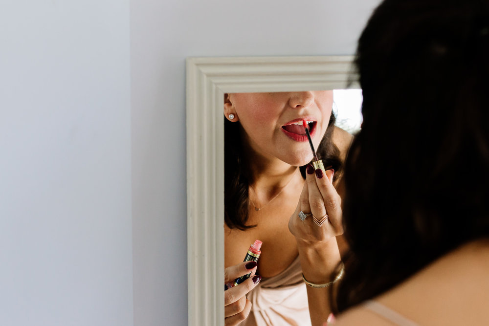 Bridesmaid doing her make up in a mirror, wedding photography.