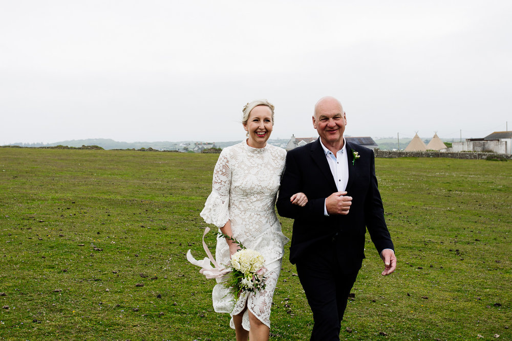 Bride with her father walking towards her groom on the headland in Anglesey
