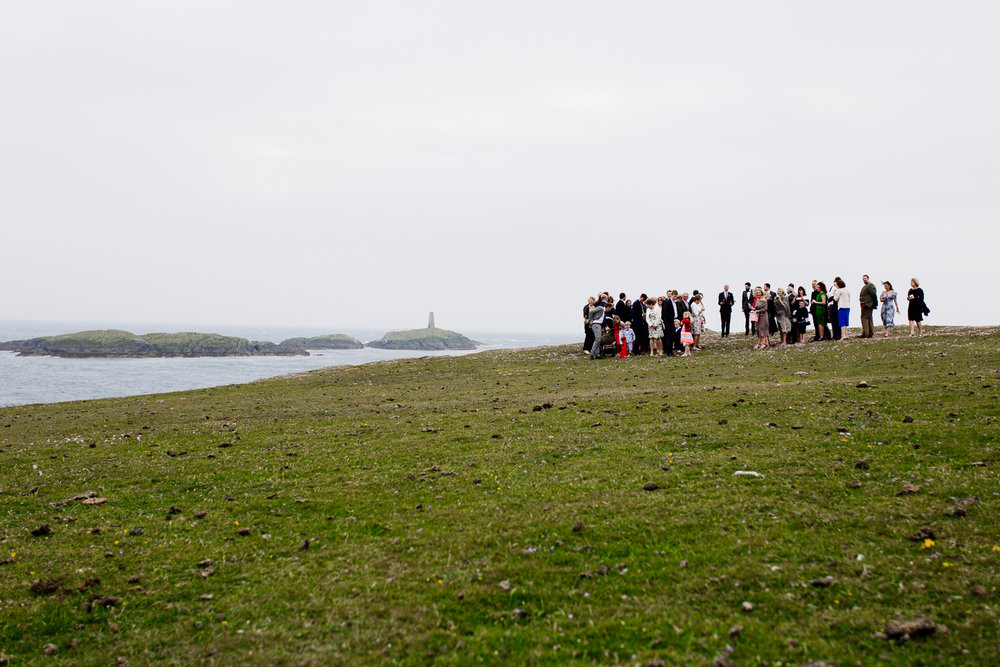 Wedding guests await the bride on the Anglesey headland overlooking the sea for an outdoor ceremony.