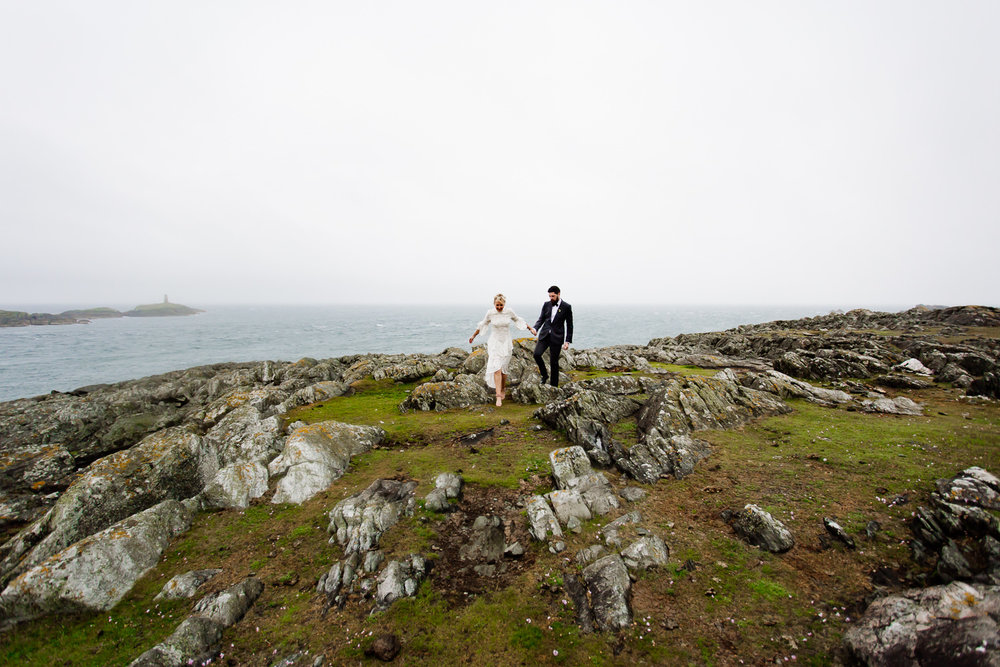 Bride and groom walking along the cliffs together at their tipi wedding in Anglesey.