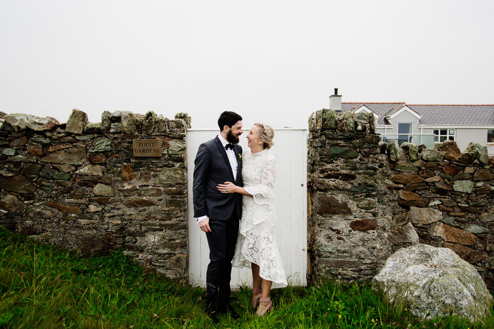 Relaxed, festival, tipi wedding in Wales, the bride and groom stood in front of a garden gate.