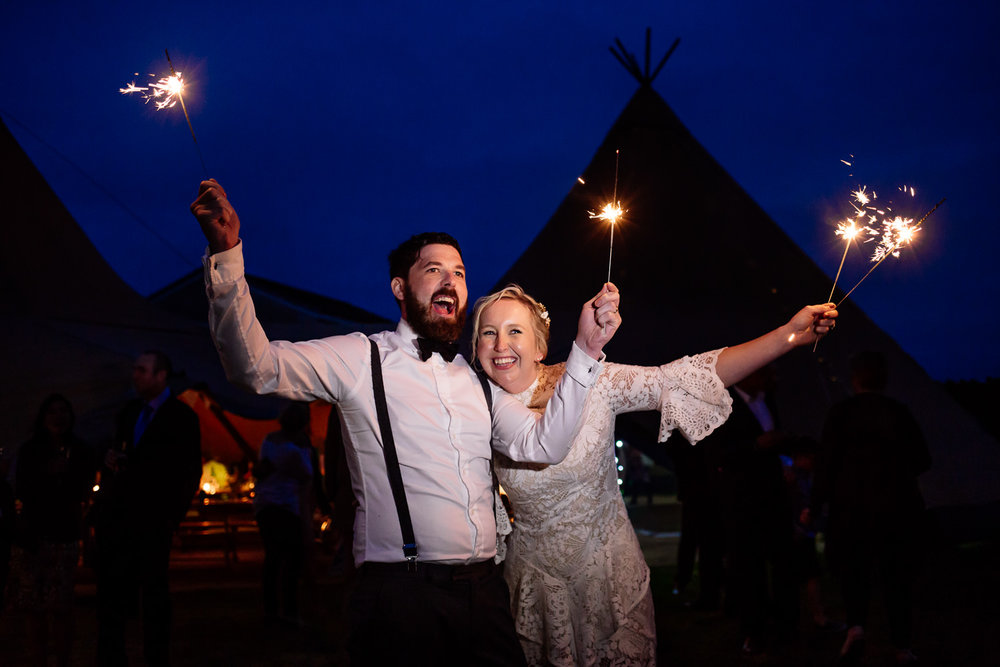 A bride and groom with sparklers in front of a tipi in Anglesey, Wales Wedding Photographer.