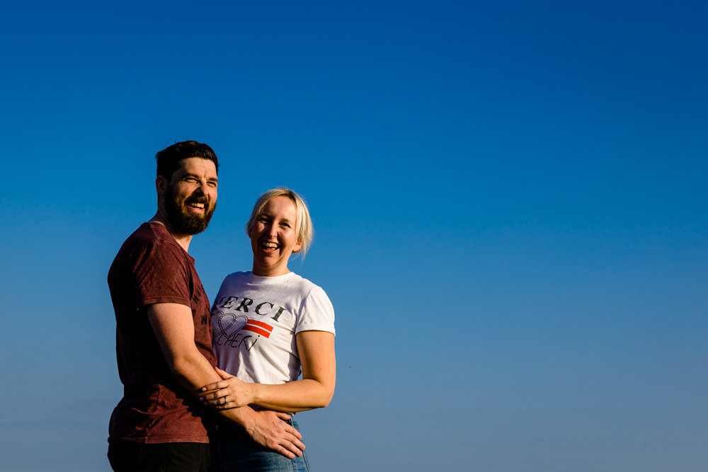 A couple laugh together on their sunny shoot in Anglesey.