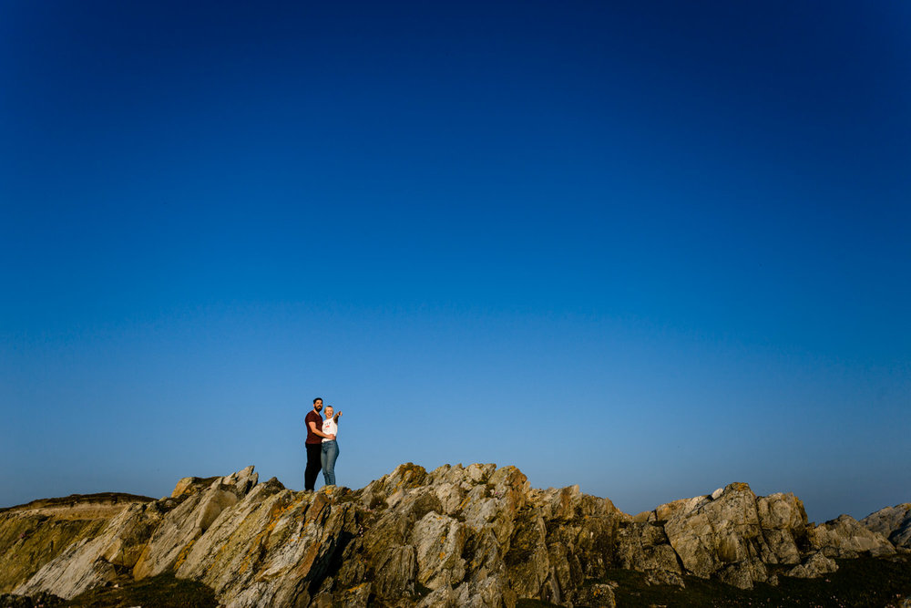 An engaged couple pointing out to sea whilst stood on the Anglesey headland on a pre wedding shoot.
